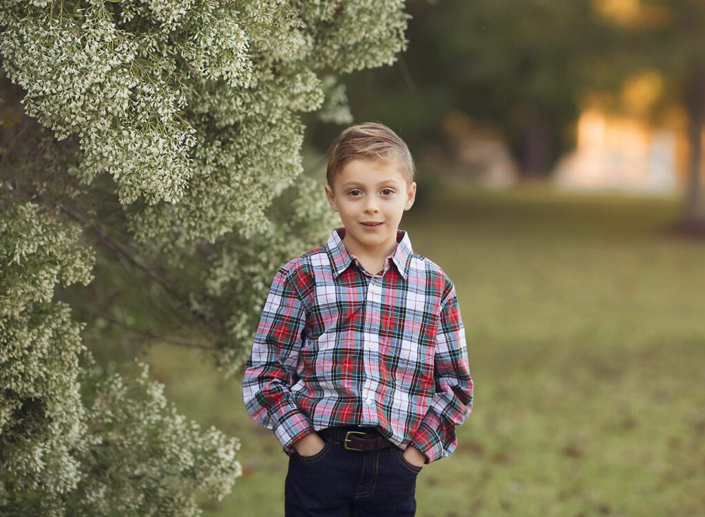 boy in paid shirt by green bush
