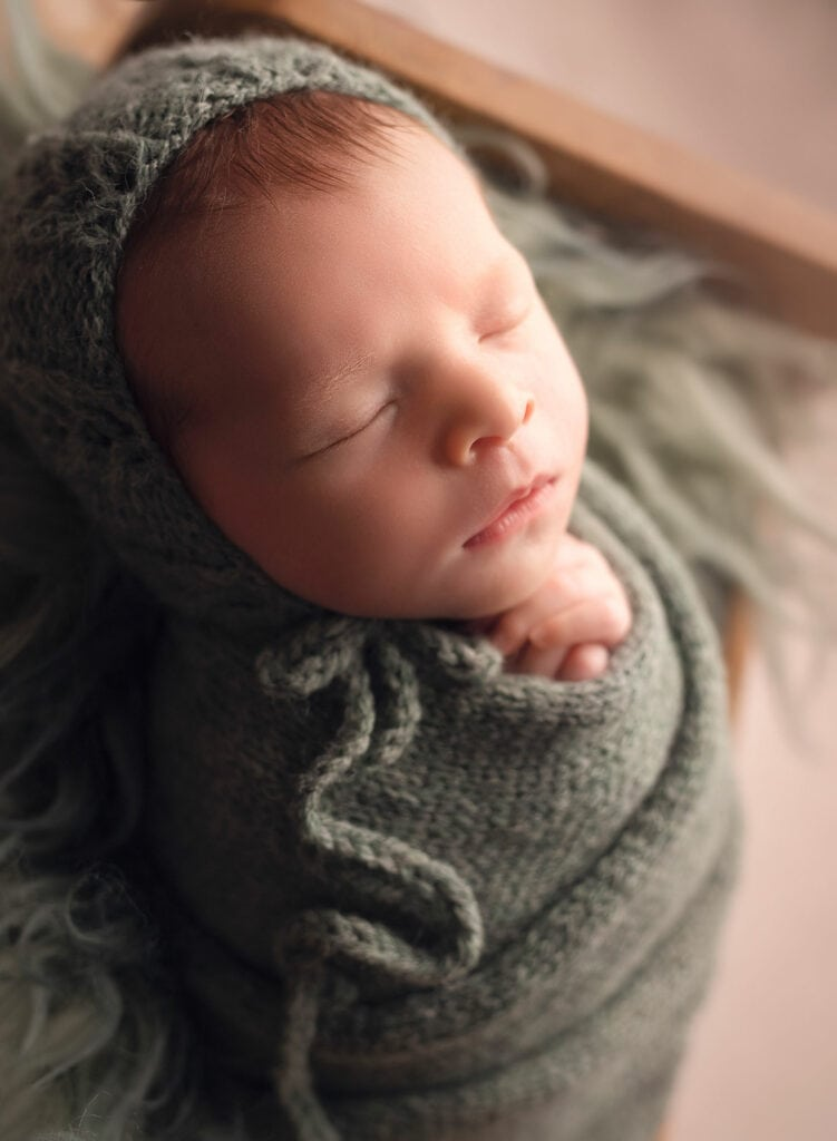 sweet profile of newborn boy in green bonnet
