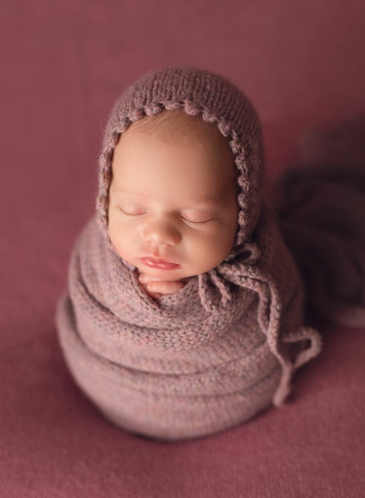 perfect newborn potato sack pose on purple backdrop