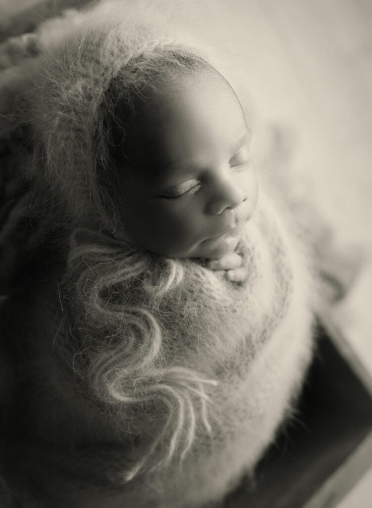 black and white photo of wrapped baby