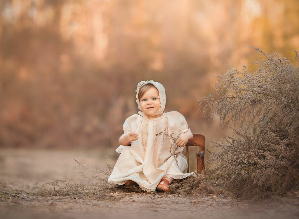 baby girl in vintage cream dress and bonnet