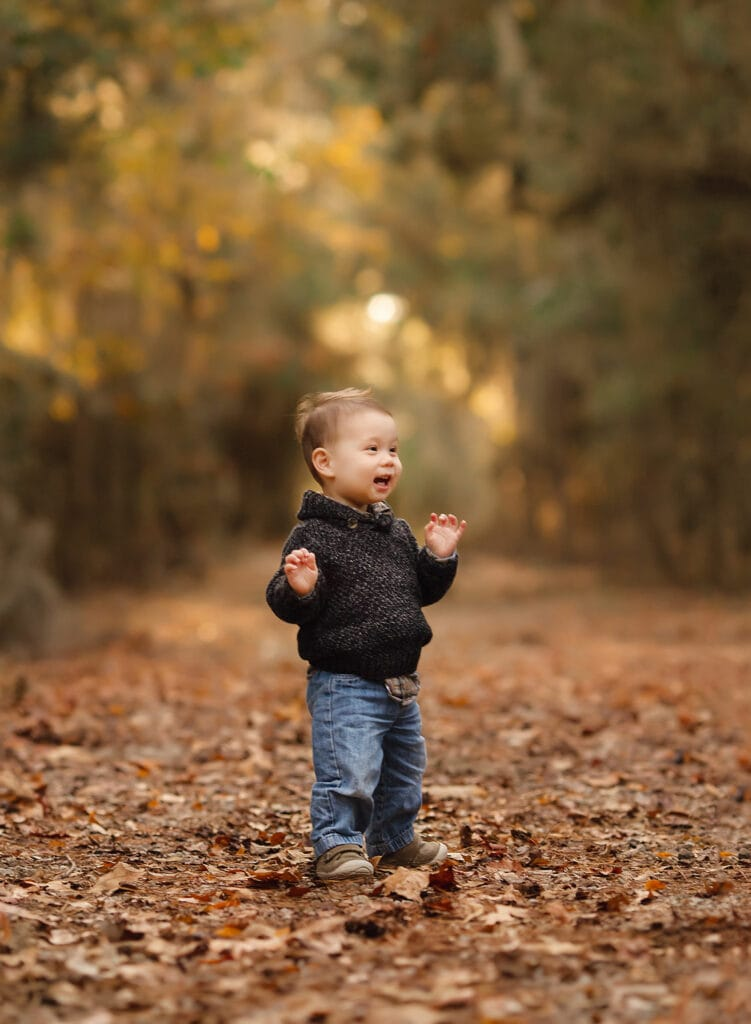 one year old boy in fall leaves