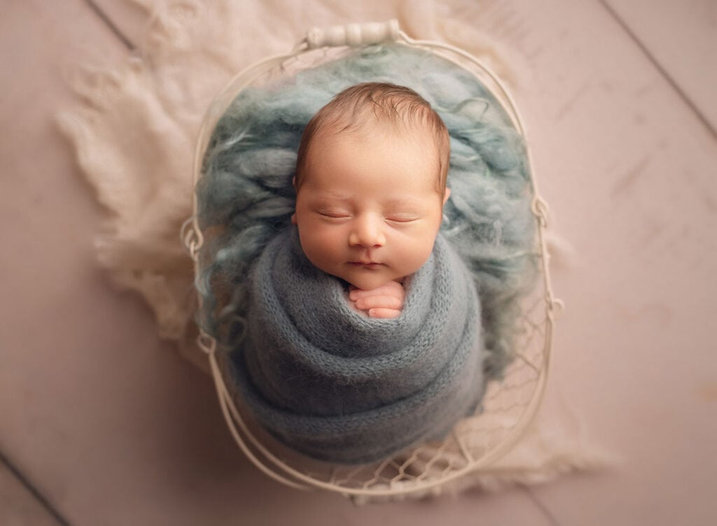 newborn boy in blue wrap