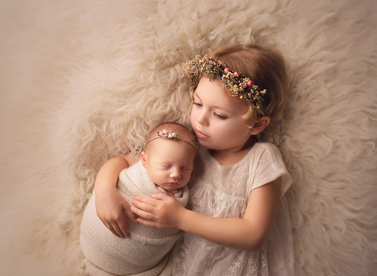 Big sister in pink flower crown holding little sister.