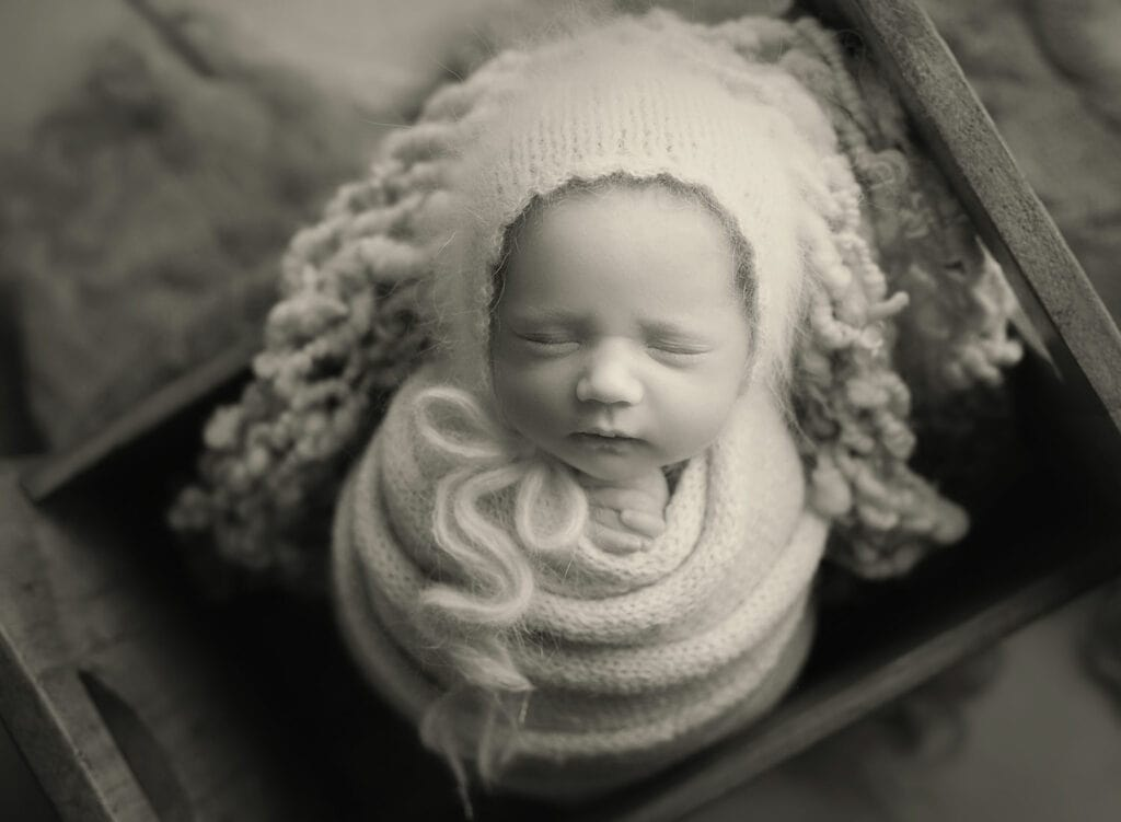 black and white photo of wrapped newborn girl in tiny bed