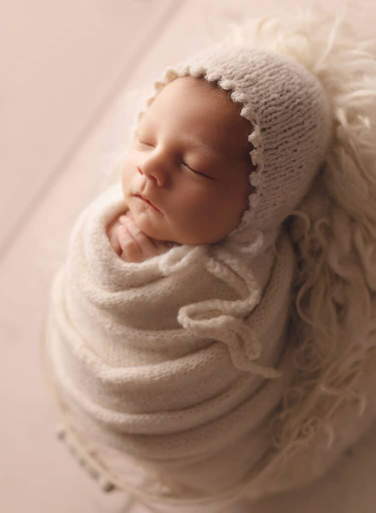 newborn girl wrapped in cream knits