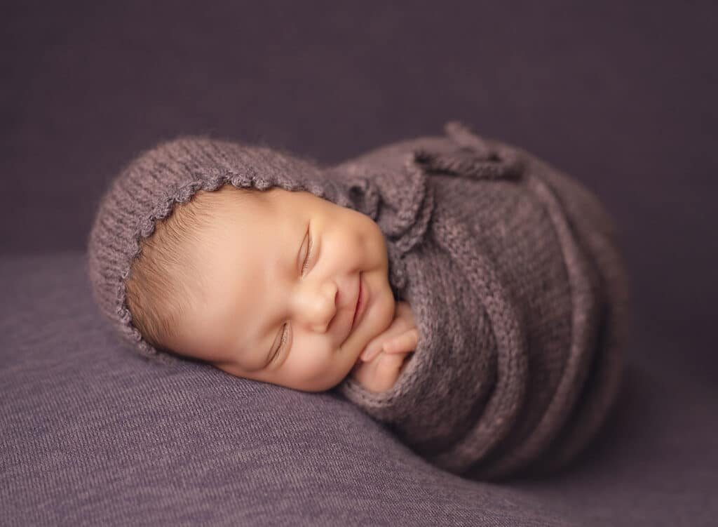 smiling newborn in purple wrap