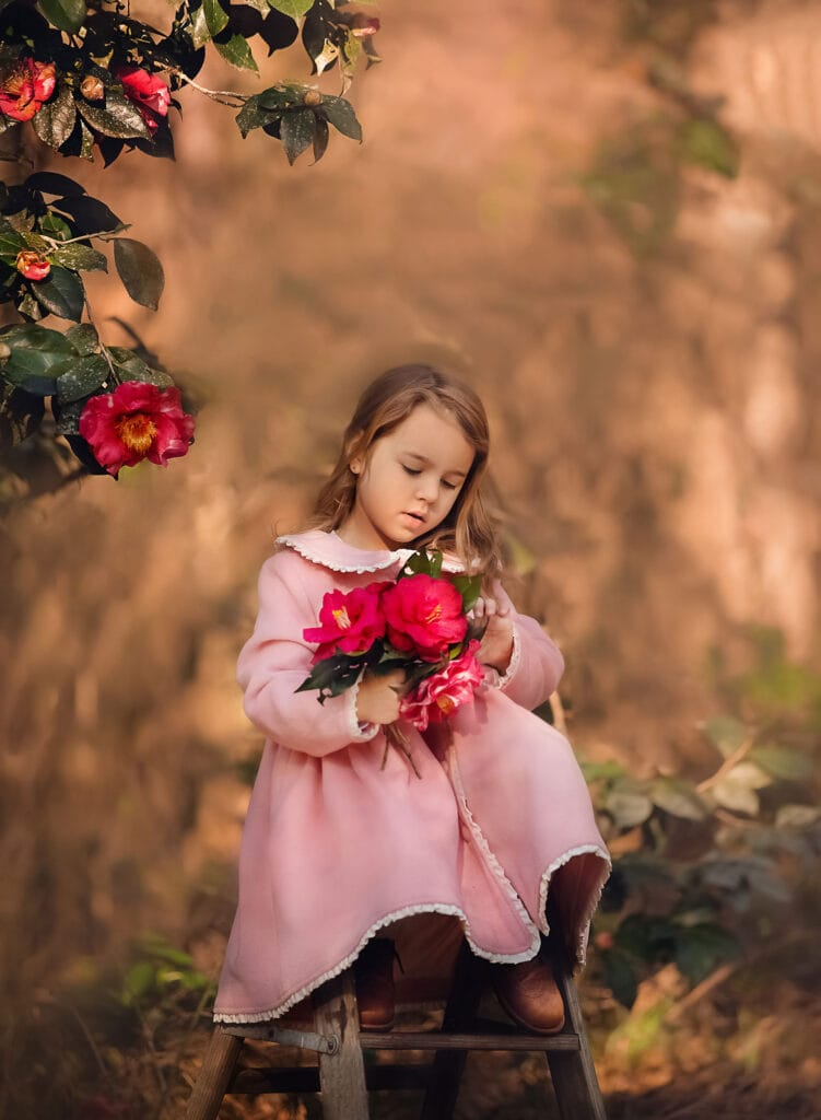 beautiful photo of girl in pink coat holding flowers