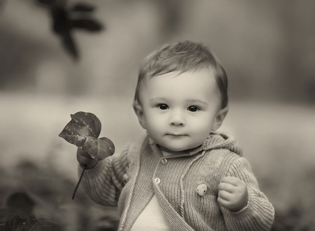 black and white photo of baby boy holding leaf