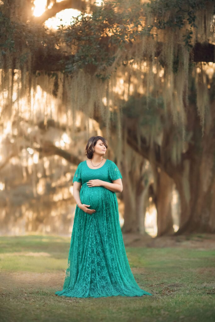 mother to be in teal gown at sunset