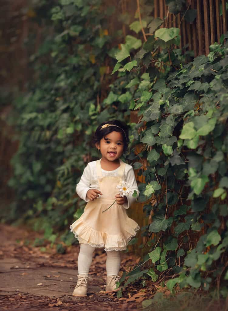 toddler in vintage yellow dress holding flower