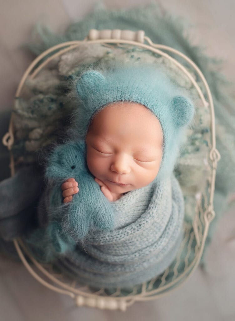 newborn baby boy in blue bear bonnet holding bear toy