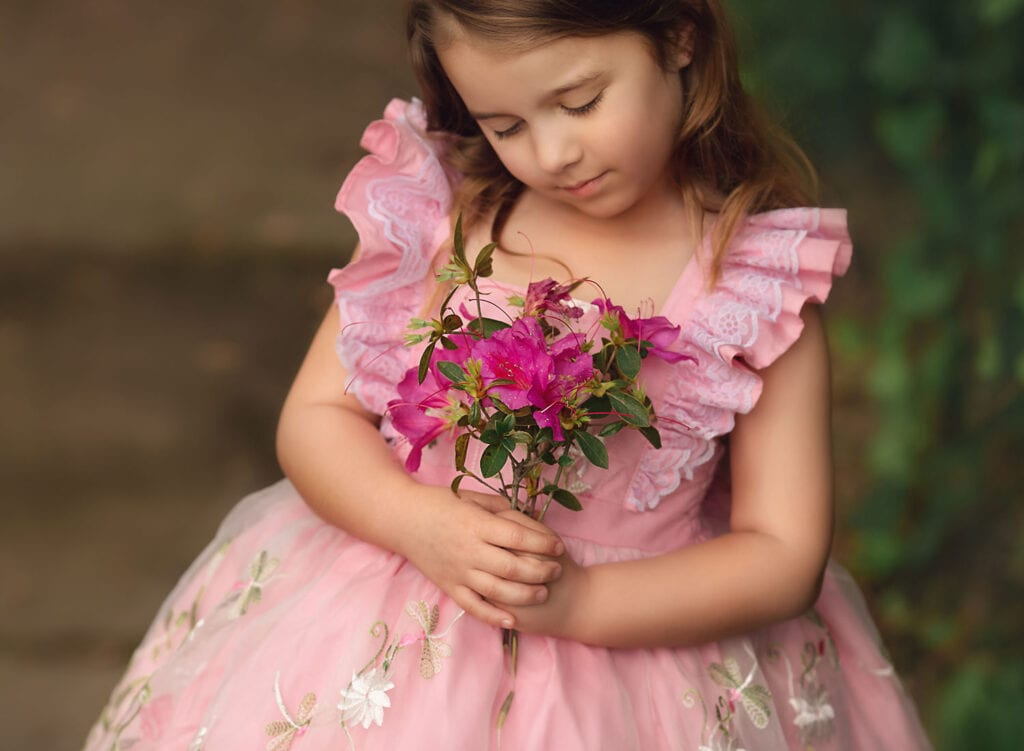 girl holding pink flowers
