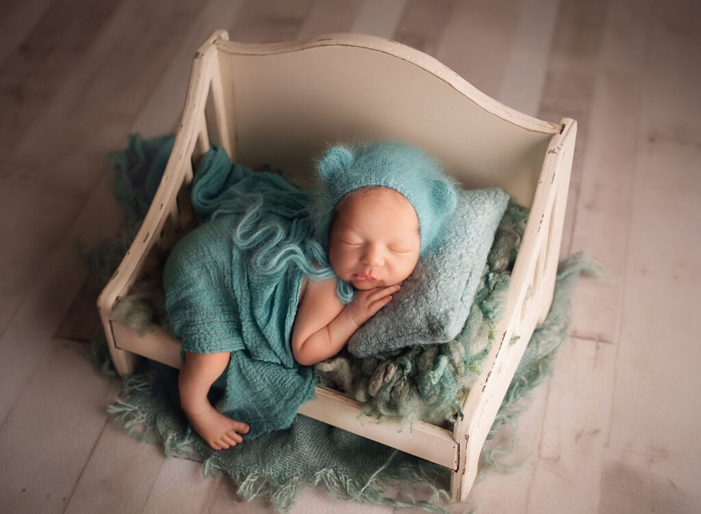 newborn boy in mint bear bonnet on little bed