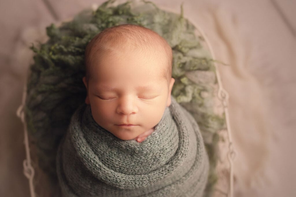 newborn boy in green knit wrap