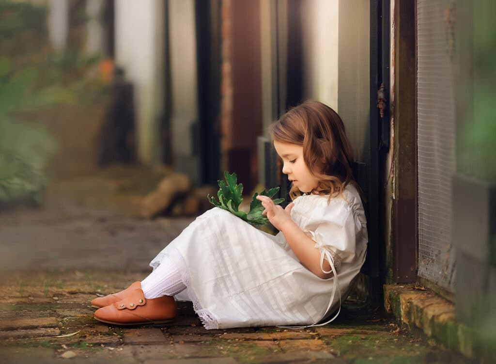 fine art photography of girl holding leaf