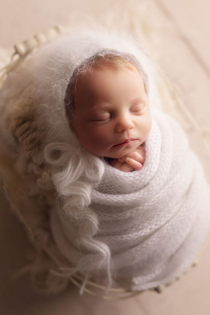 sleeping newborn girl in basket