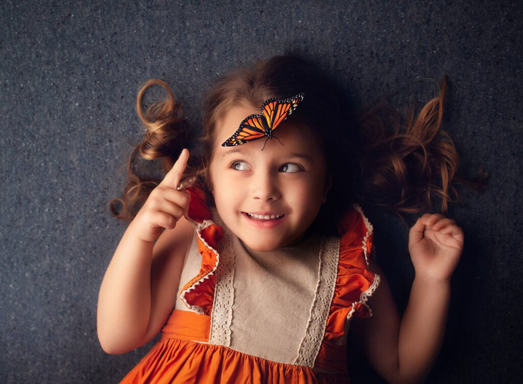 fine art photograph of girl with butterfly on forehead