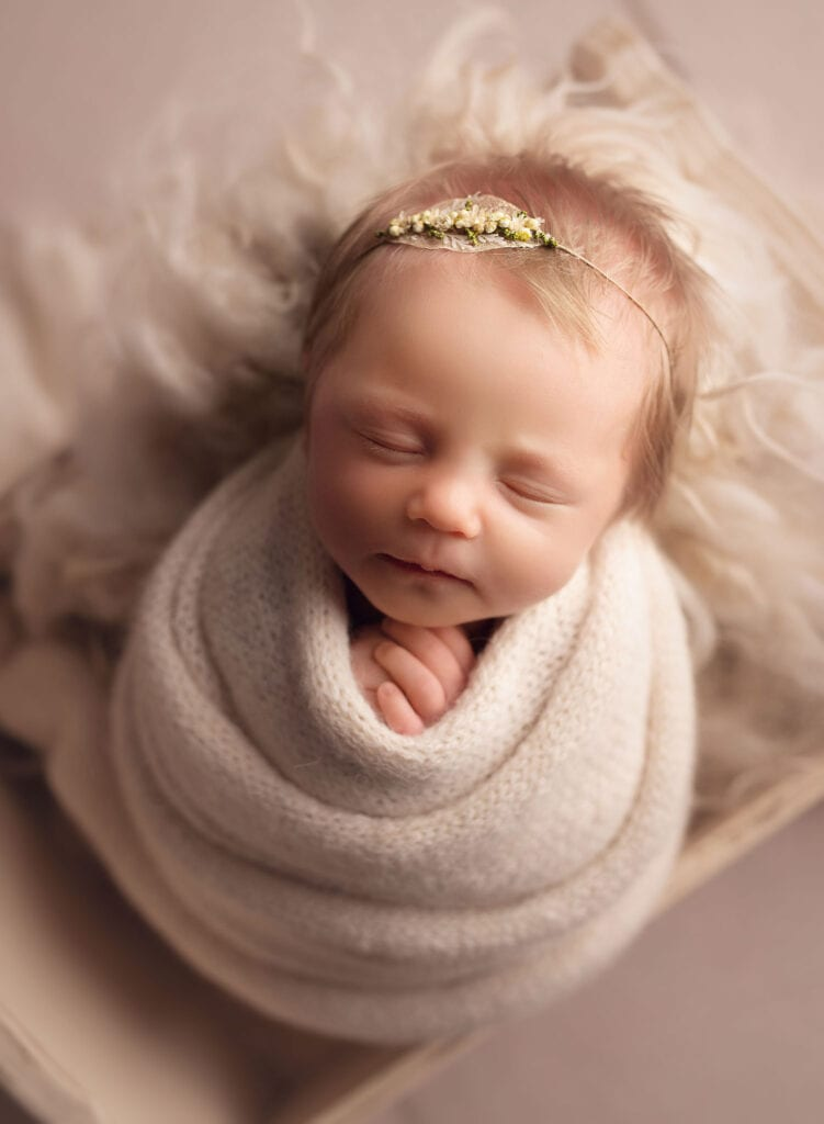 newborn girl in cream wrap in tiny bed