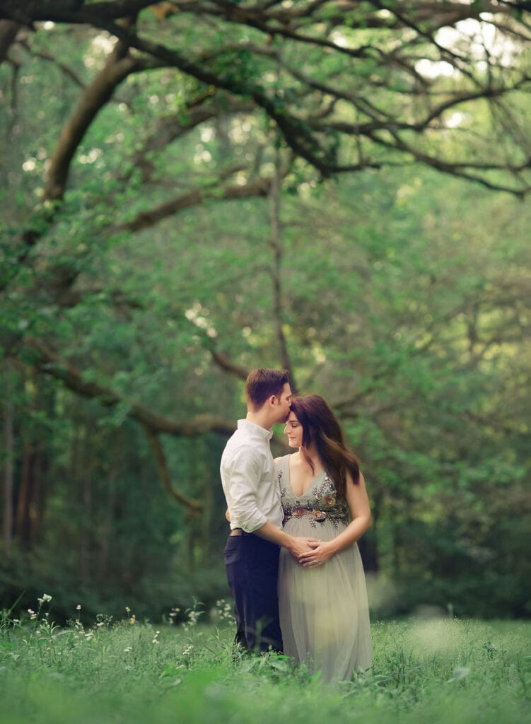 stunning photo of couple expecting baby girl under live oak branches