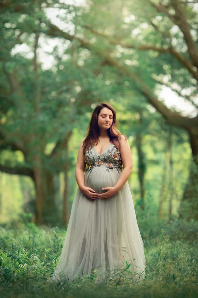 fine art maternity photo in front of large oak trees