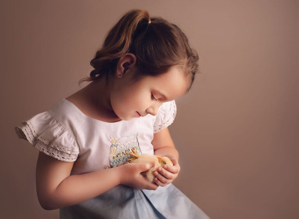 little girl and baby chick