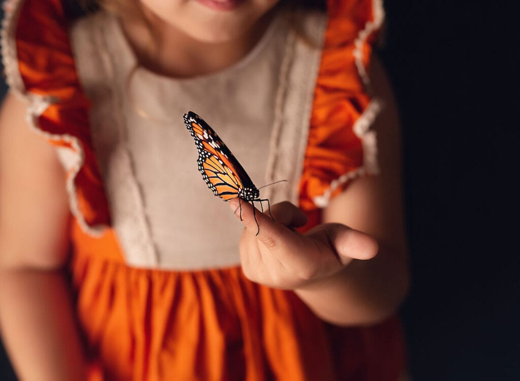 precious photo of girl holding monarch butterfly on tip of finger