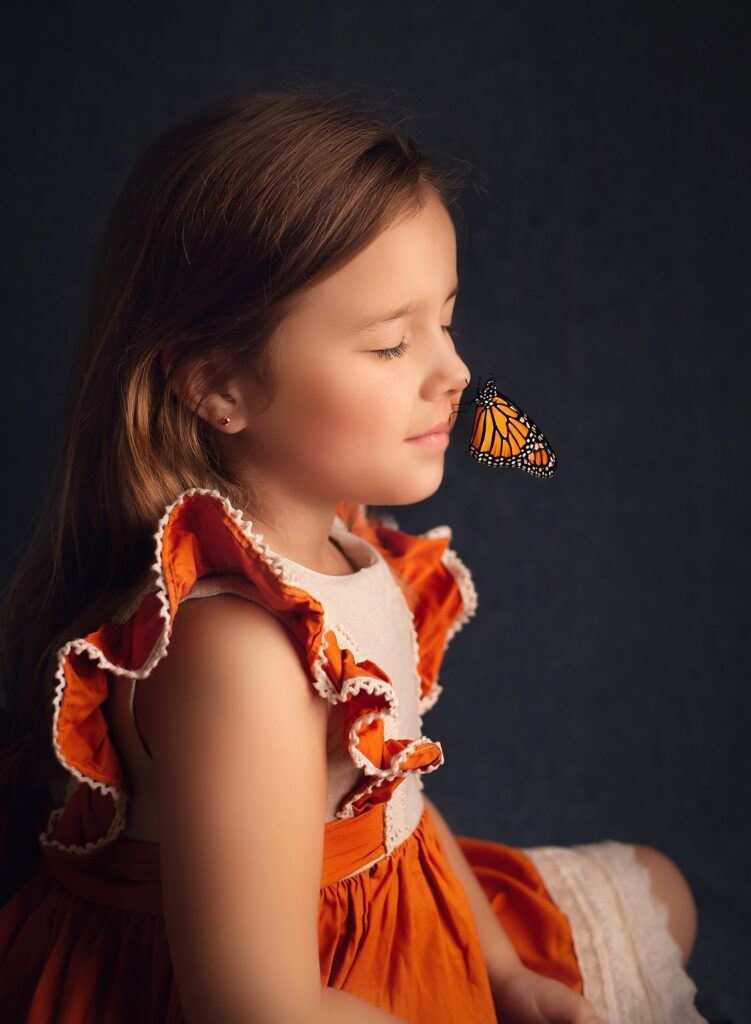Peaceful photo of girl in orange dress with butterfly on her nose