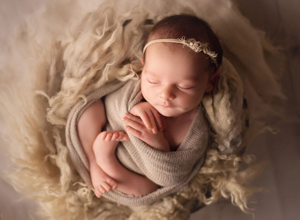 newborn wrapped in cozy nest