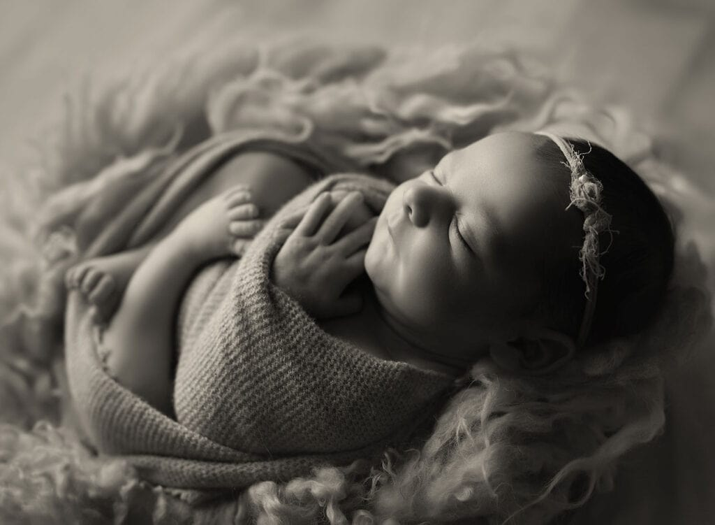 black and white photo of newborn girl in nest