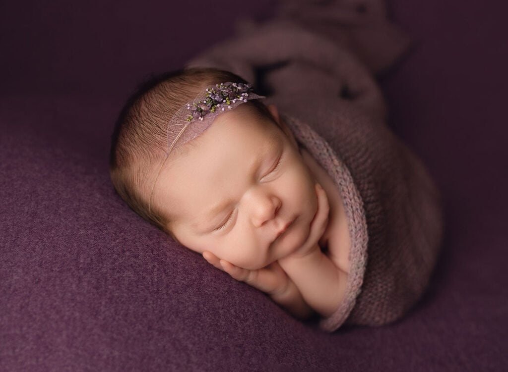 newborn girl on purple drop