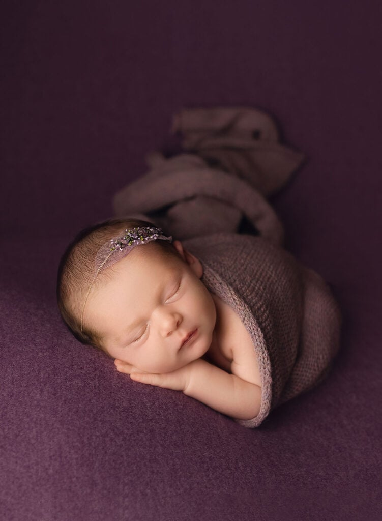 fine art newborn photo of baby girl in purple