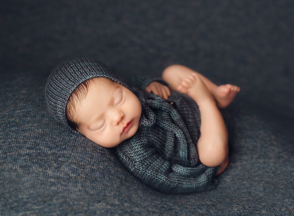 newborn baby boy in blue knit outfit