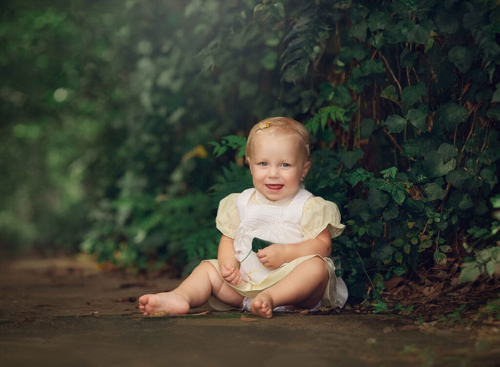 smiling one year old girl in yellow dress
