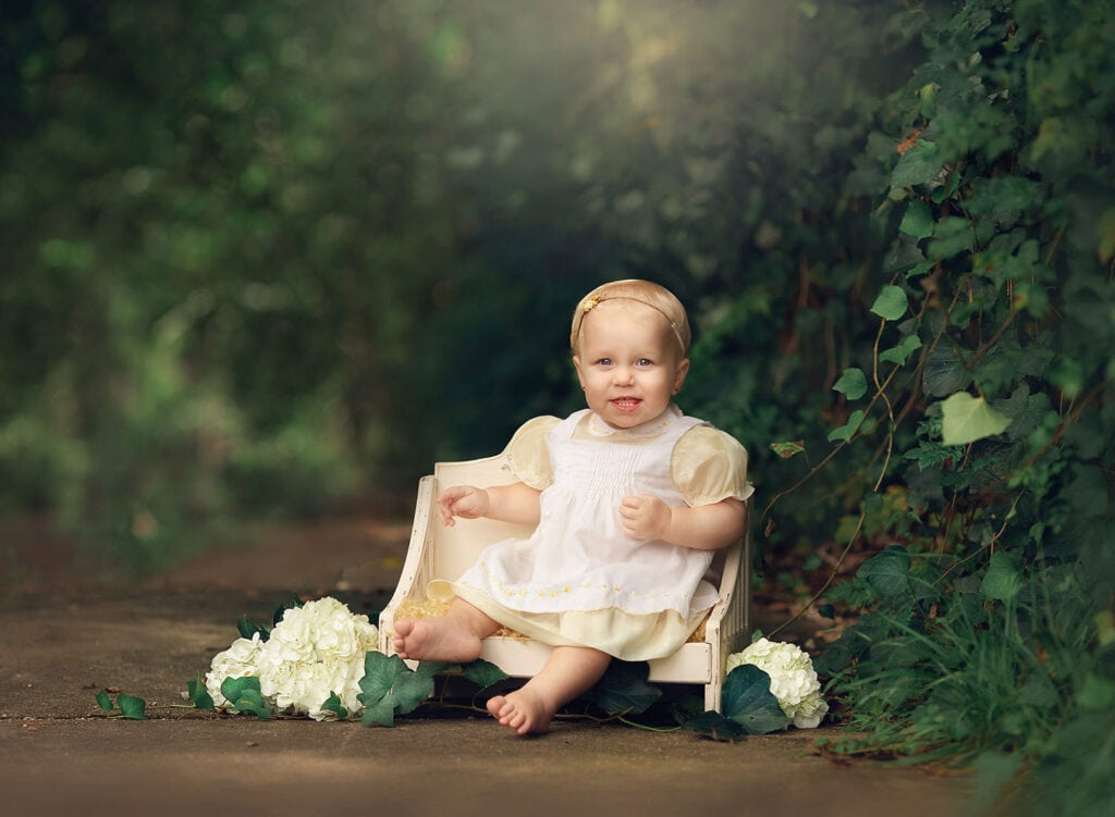 Fine art photo of one year old girl on white bench