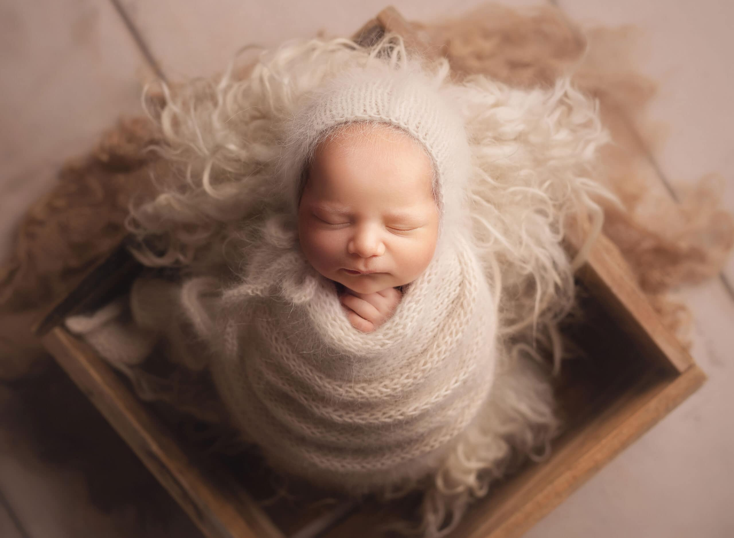 Fine art newborn photo of boy in cream angora wrap