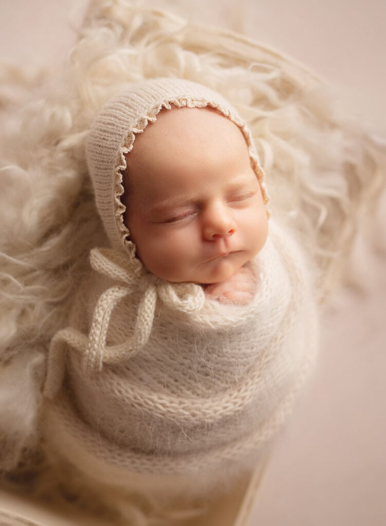 newborn girl in cream wrap and bonnet