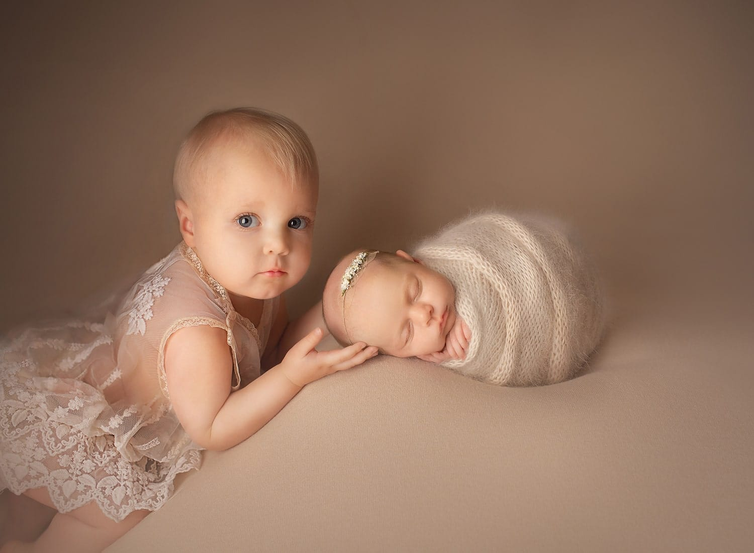 Fine art photo of big sister with newborn little sister