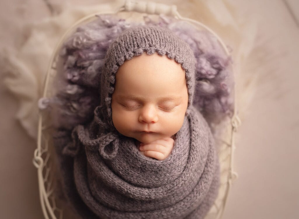 newborn girl in purple bonnet and wrap