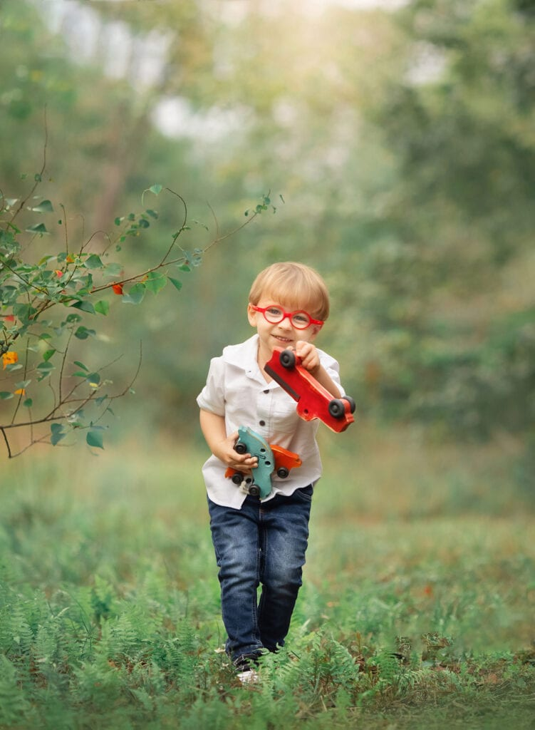 little boy holding toy cars
