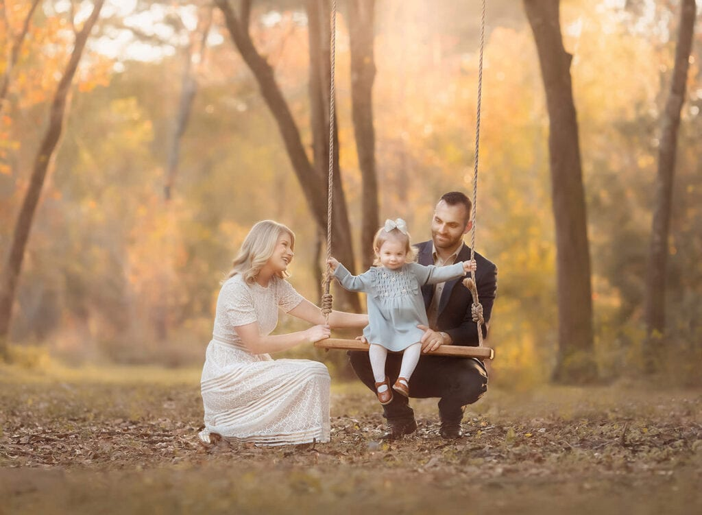 little girl on swing next to mom and dad